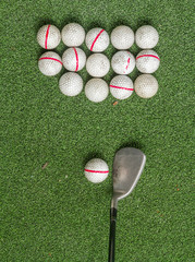 Old golf balls and iron on artificial grass in driving range.