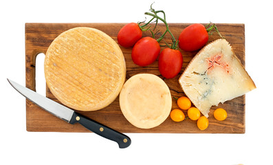Farm produced rustic cheeses on board with red and yellow tomato