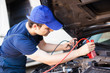 Mechanic using cables to start-up a car engine