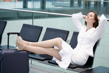 Frau sitzt in der Wartehalle , Füße auf Koffer