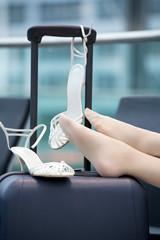 Frau sitzt in der Wartehalle Füße auf Koffer