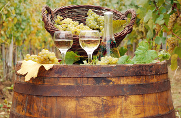 white wine and grape on wooden barrel