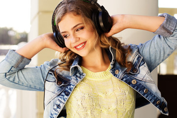 Young happy teenager is wearing headphones