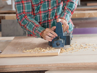Carpenter Using Electric Planer On Wooden Plank
