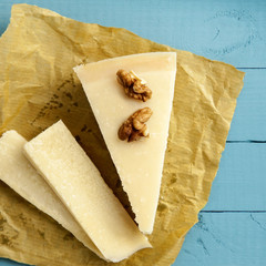 Italian Parmesan Parmigiano Cheese with  Walnut  on Blue Wooden