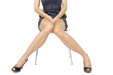 Junge Frau im Minikleid sitzt auf dem Stuhl