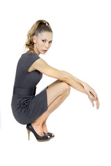 Junge Frau im Minikleid , Hocken