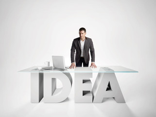 Portrait of a businessman leaning on IDEA table
