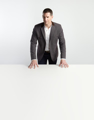 Portrait of a businessman standing behind table