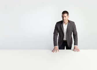 Businessman standing behind table