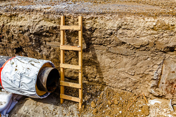 Wooden ladder in a fresh trench, layers of soil