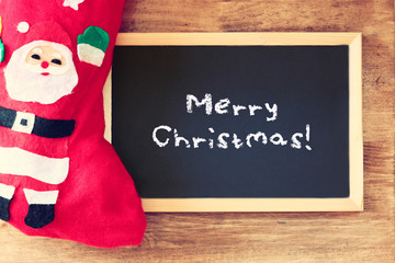 red sock and blackboard with merry christams greeting