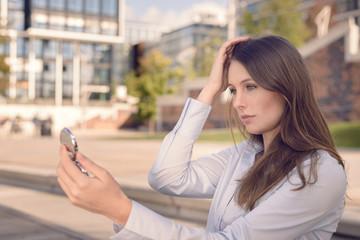 Junge attraktive Frau überprüft ihr Aussehen in einem Spiegel