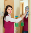 woman cleaning  mirror  with cleanser at home
