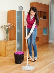 Smiling  woman washing  floor with mop