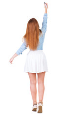 back view of writing beautiful redhead woman. Young girl in dres
