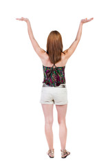 Back view of Beautiful woman in jeans looking at wall and Holds