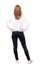 back view of standing young beautiful  blonde woman in jeans.