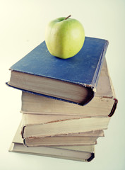 stack of old hardcover books with green apple