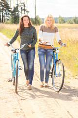 Two friends walking with bicycles