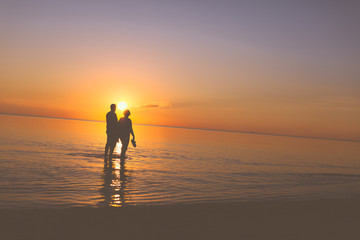 Senior couple strolling at sunset