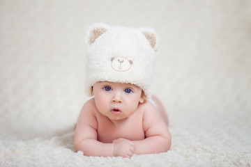 Baby lying on a soft bed cover with cap