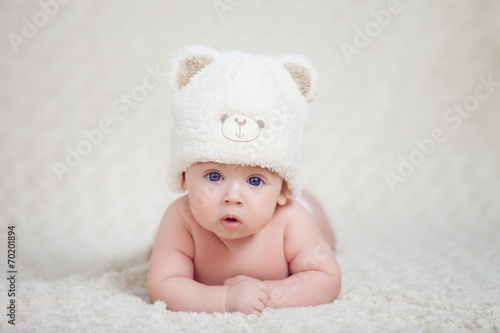 Fototapeta Baby lying on a soft bed cover with cap