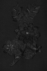 Black flower lace pattern on black fabric.
