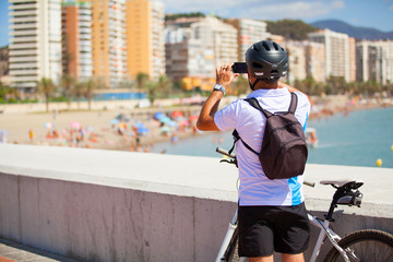 Cyclist taking a photo of the beach