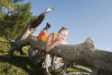 Junge Frau liegt auf Baumstamm