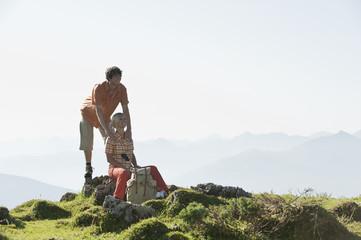 Junges Paar sitzt auf Felsen, lächelnd.