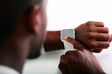 Closeup image of a man pointing on wristwatch