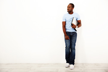 Pensive african man standing with laptop over white background