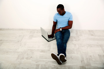 Portrait of african man sitting on the floor and using laptop