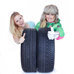 Women presenting sommer and winter tyres