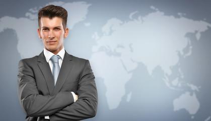 Businessmann vor Blauem Hintergrund mit Weltkarte