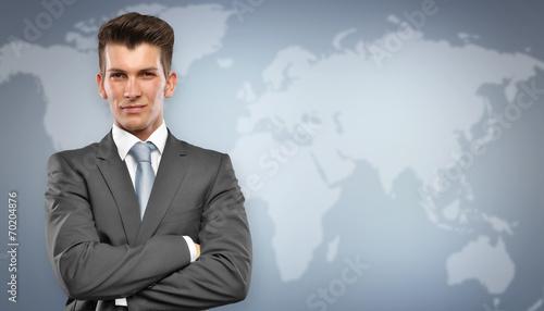 canvas print picture Businessmann vor Blauem Hintergrund mit Weltkarte