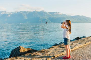 Cute little girl looking in binoculars on sunset