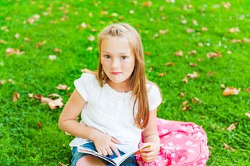 Cute little girl reading a book in a park after school