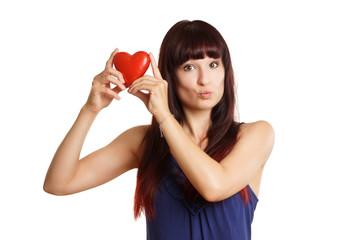 Frau macht Kussmund und hält rotes Herz