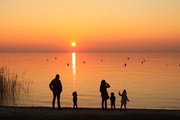 Famiglia al tramonto sul lago