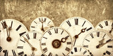 Various vintage clock faces in front of an old wall