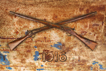Two crossed vintage wooden rifles against a rusty background