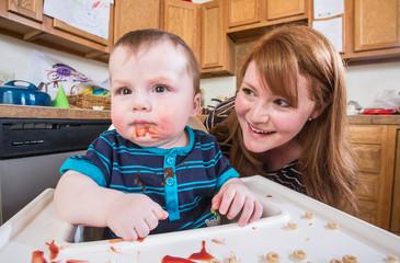 Woman Feeds Baby in Kitchen