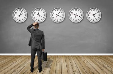 Mann steht im raum mit Uhren