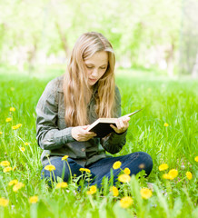 girl sitting on grass with dandelions and reading a book