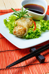 fried spring rolls on red bamboo mat