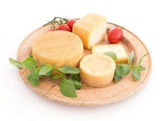 Cheeseboard with rustic cheeses and tomatoes, over white