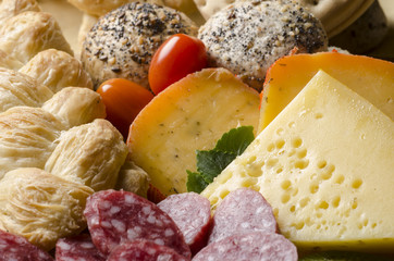 assorted cheeses with bread, tomatoes and sliced salami