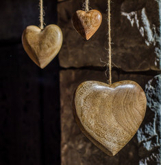 Wooden hearts and old stone wall